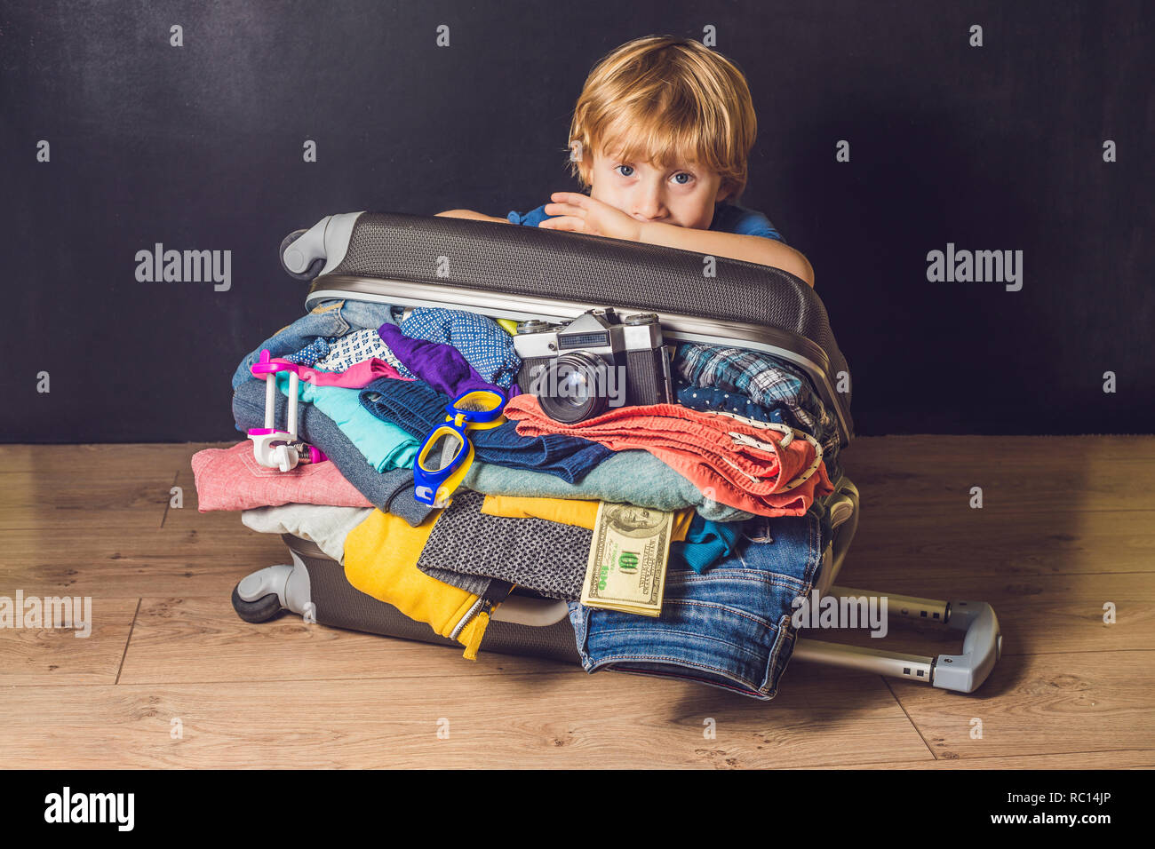 Baby boy and Travel Suitcase. Kid and Luggage Packed for Vacation Full of Clothes, Child and Family Trip - Stock Image