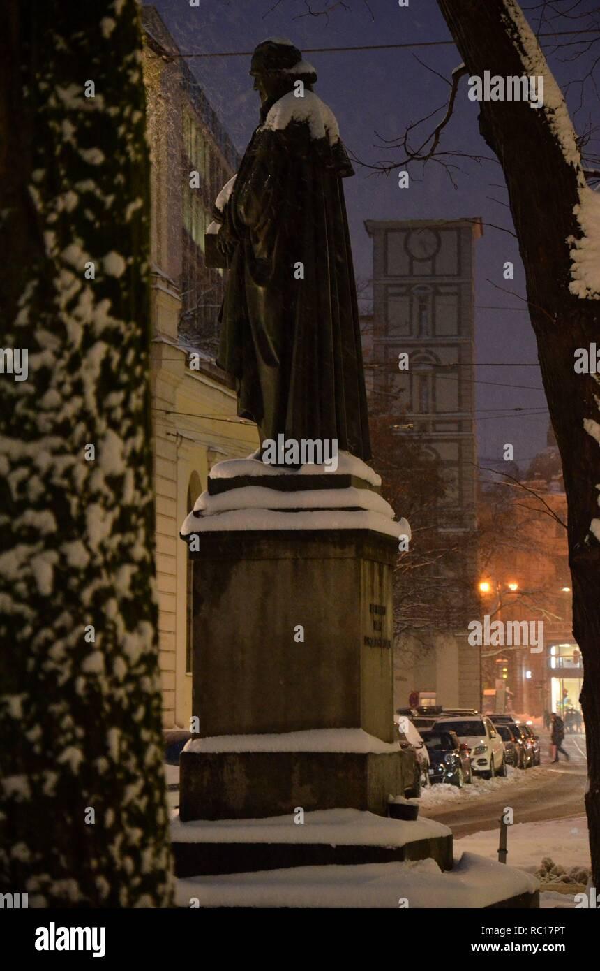 Winterszene am Promenadeplatz in München (Bayern, Deutschland) mit Winterbeleuchtung: Statue des Lorenz von Westenrieder, im Hintergrund Maxburg - Stock Image