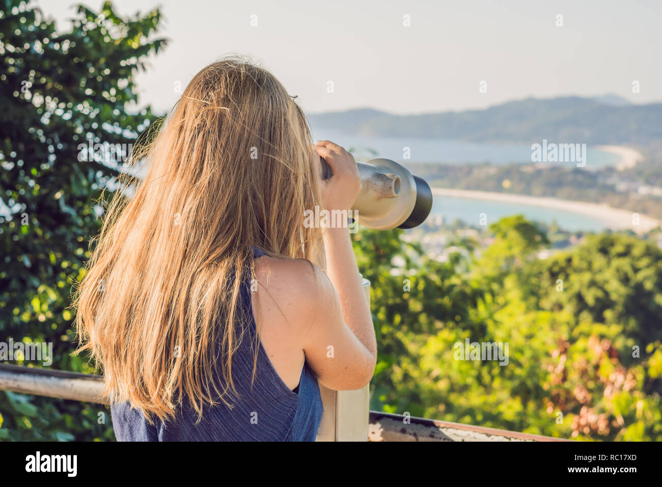 young beautiful blond woman enjoy the view with an coin operated binoculars. The water and the sky is blue. she wears a white dress and sunglasses. she feels good, is smiling and look to the horizon - Stock Image
