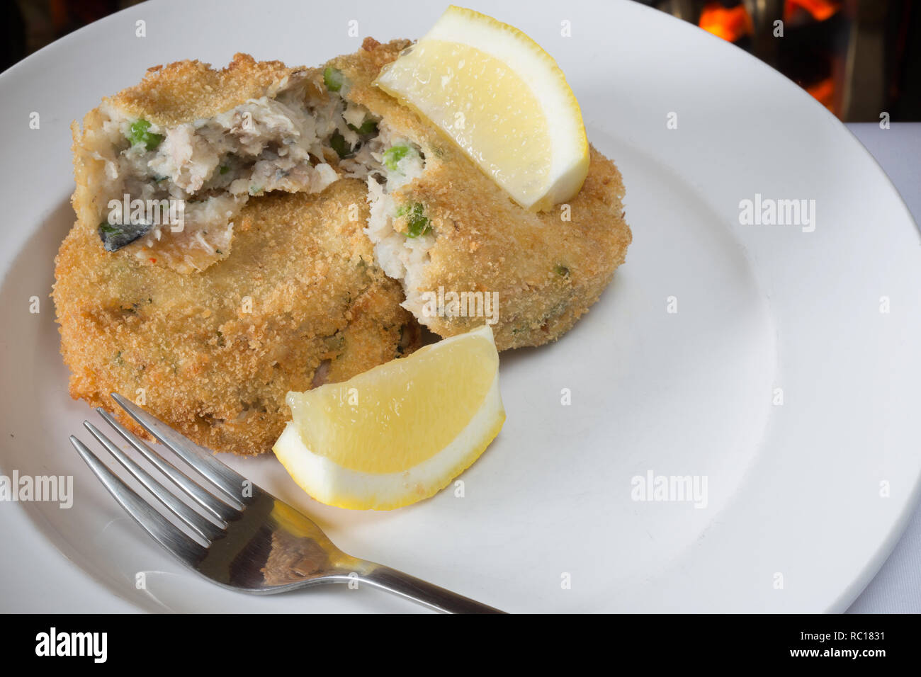Homemade Breaded Mackerel and pea fishcake with Lemon wedge garnish - Stock Image