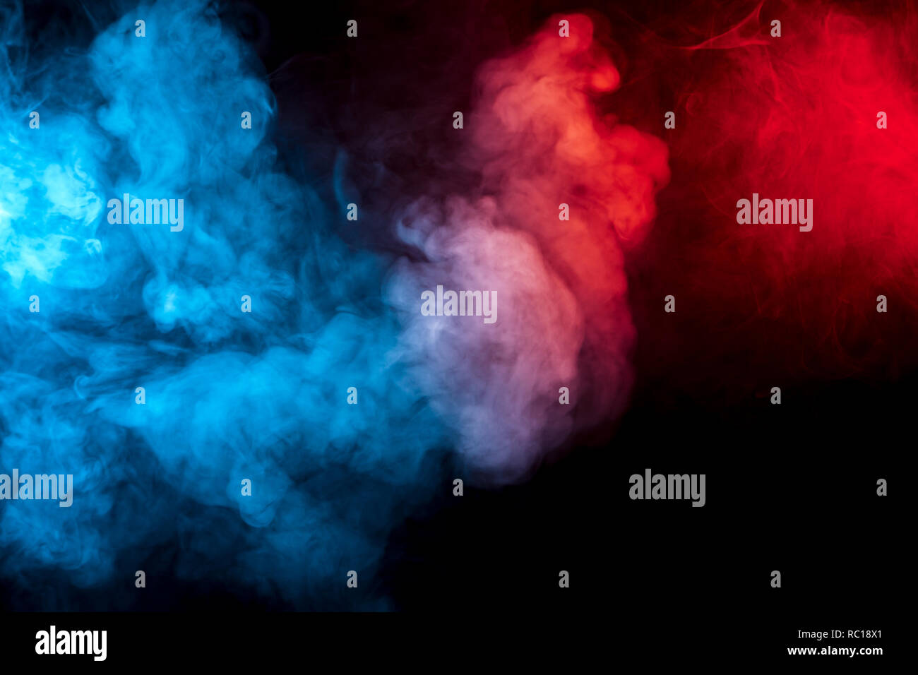 Clouds of isolated colored smoke: blue, red, orange, pink; scrolling on a black background in the dark close up. Stock Photo