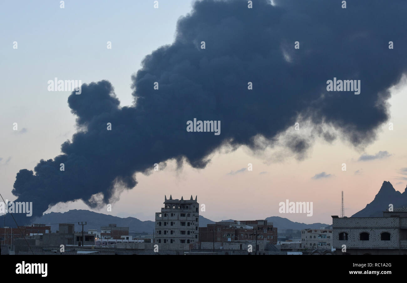 Aden, Yemen. 12th Jan, 2019. Photo taken on Jan. 12, 2019 shows heavy smoke from a state-owned oil refinery in Aden, Yemen. A new powerful explosion hit the the state-owned oil refinery in Aden on Saturday evening, injuring at least 15 people, a security official told Xinhua. Credit: Murad Abdo/Xinhua/Alamy Live News Credit: Xinhua/Alamy Live News - Stock Image