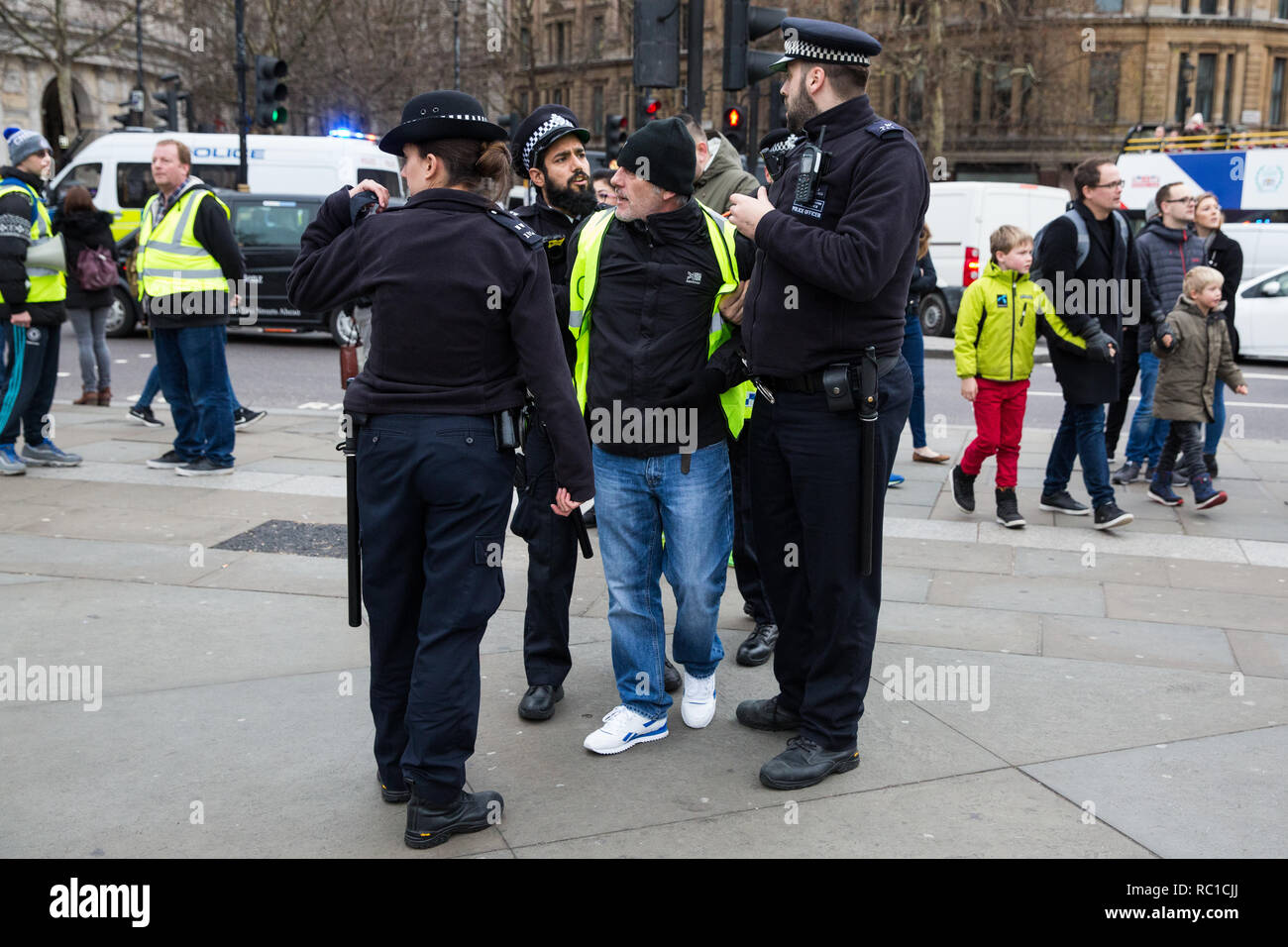 London, UK. 12th January, 2019. Police officers hold a man as they keep order between around fifty supporters of far-right group Liberty Defenders and hundreds of protesters taking part in a 'Britain is Broken: General Election Now' demonstration organised by the People's Assembly Against Austerity. Some members of both groups were wearing yellow vests in solidarity with the 'gilets jaunes' in France. Credit: Mark Kerrison/Alamy Live News - Stock Image