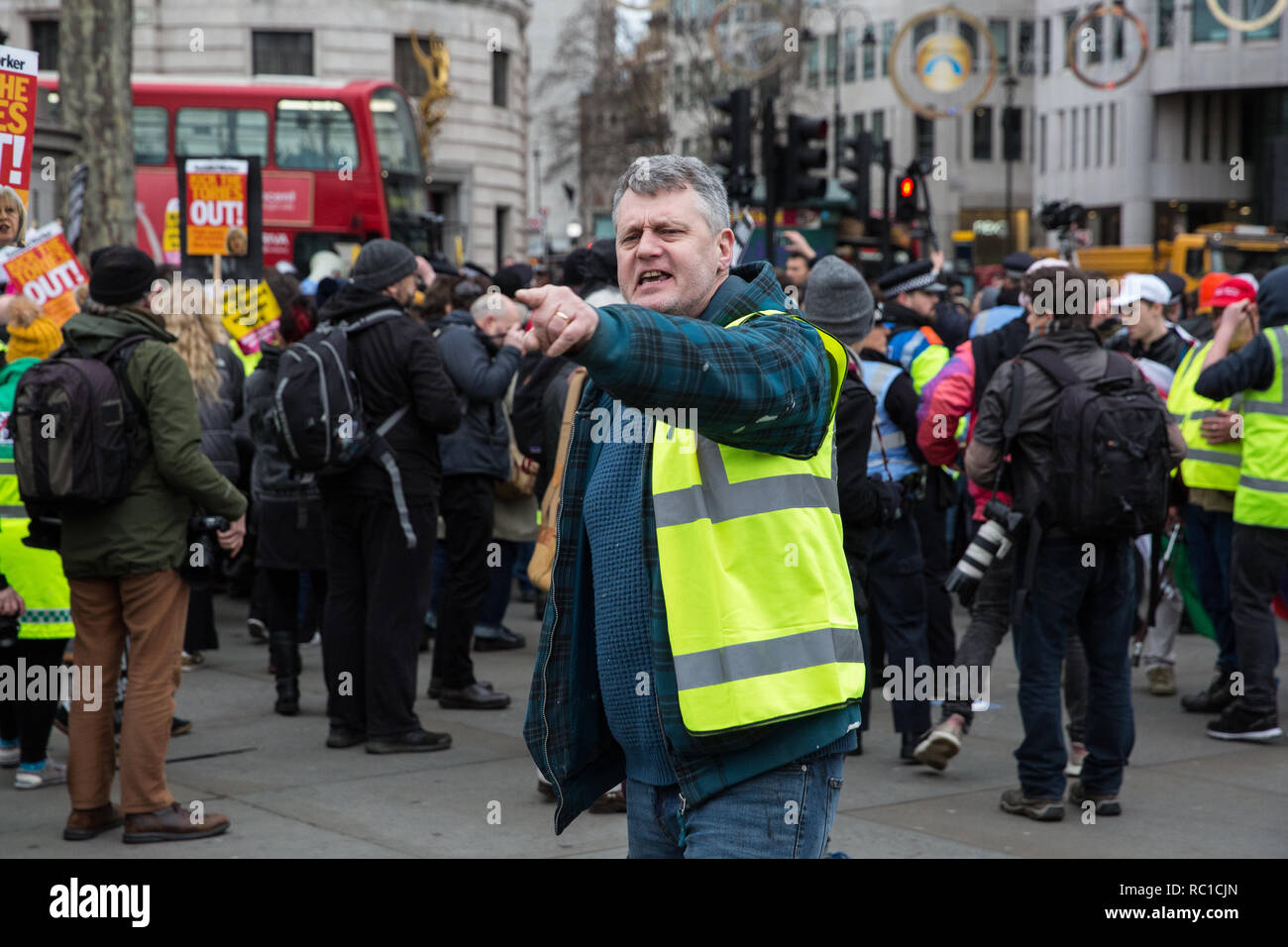 London, UK. 12th January, 2019. A man wearing a yellow vest shouts at protesters taking part in a 'Britain is Broken: General Election Now' demonstration organised by the People's Assembly Against Austerity. Some members of both groups were wearing yellow vests in solidarity with the 'gilets jaunes' in France. Credit: Mark Kerrison/Alamy Live News - Stock Image
