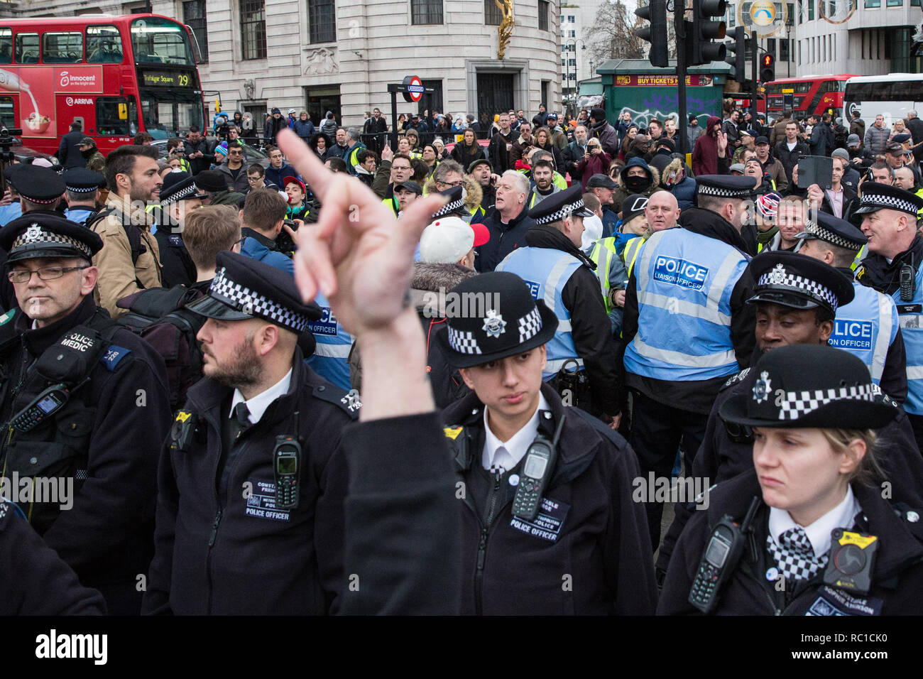 London, UK. 12th January, 2019. A woman makes a rude gesture towards around fifty supporters of far-right group Liberty Defenders being kept apart by police officers from hundreds of protesters taking part in a 'Britain is Broken: General Election Now' demonstration organised by the People's Assembly Against Austerity. Some members of both groups were wearing yellow vests in solidarity with the 'gilets jaunes' in France. Credit: Mark Kerrison/Alamy Live News - Stock Image