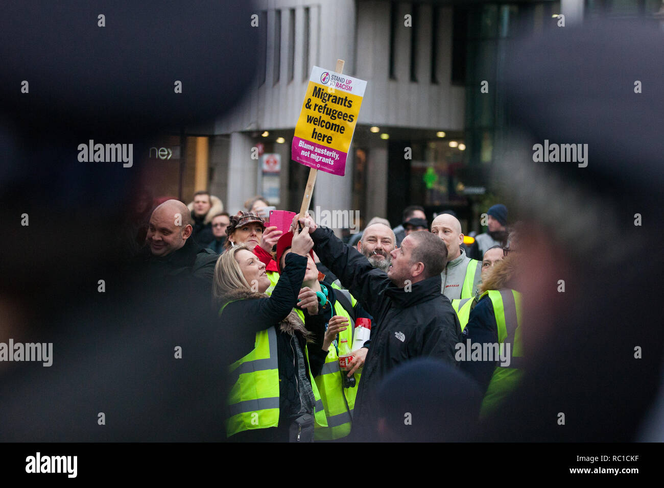 London, UK. 12th January, 2019. Max Hammet-Millay (c, partially obscured) stands among around fifty supporters of far-right group Liberty Defenders being kept apart by police from hundreds of protesters taking part in a 'Britain is Broken: General Election Now' demonstration organised by the People's Assembly Against Austerity. Some members of both groups were wearing yellow vests in solidarity with the 'gilets jaunes' in France. Credit: Mark Kerrison/Alamy Live News - Stock Image