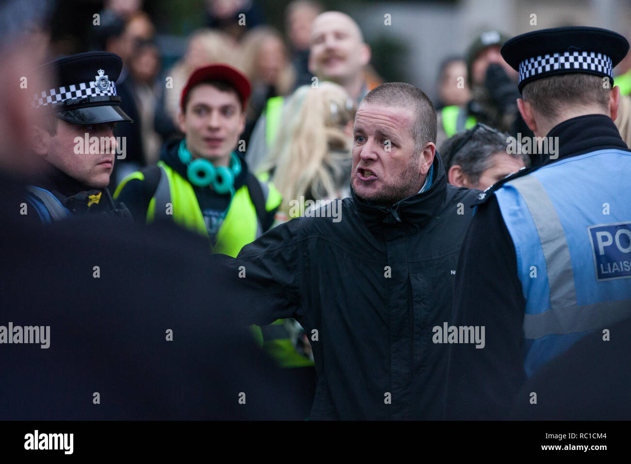 London, UK. 12th January, 2019. Police officers keep order between around fifty supporters of far-right group Liberty Defenders and hundreds of protesters taking part in a 'Britain is Broken: General Election Now' demonstration organised by the People's Assembly Against Austerity. Some members of both groups were wearing yellow vests in solidarity with the 'gilets jaunes' in France. Credit: Mark Kerrison/Alamy Live News - Stock Image
