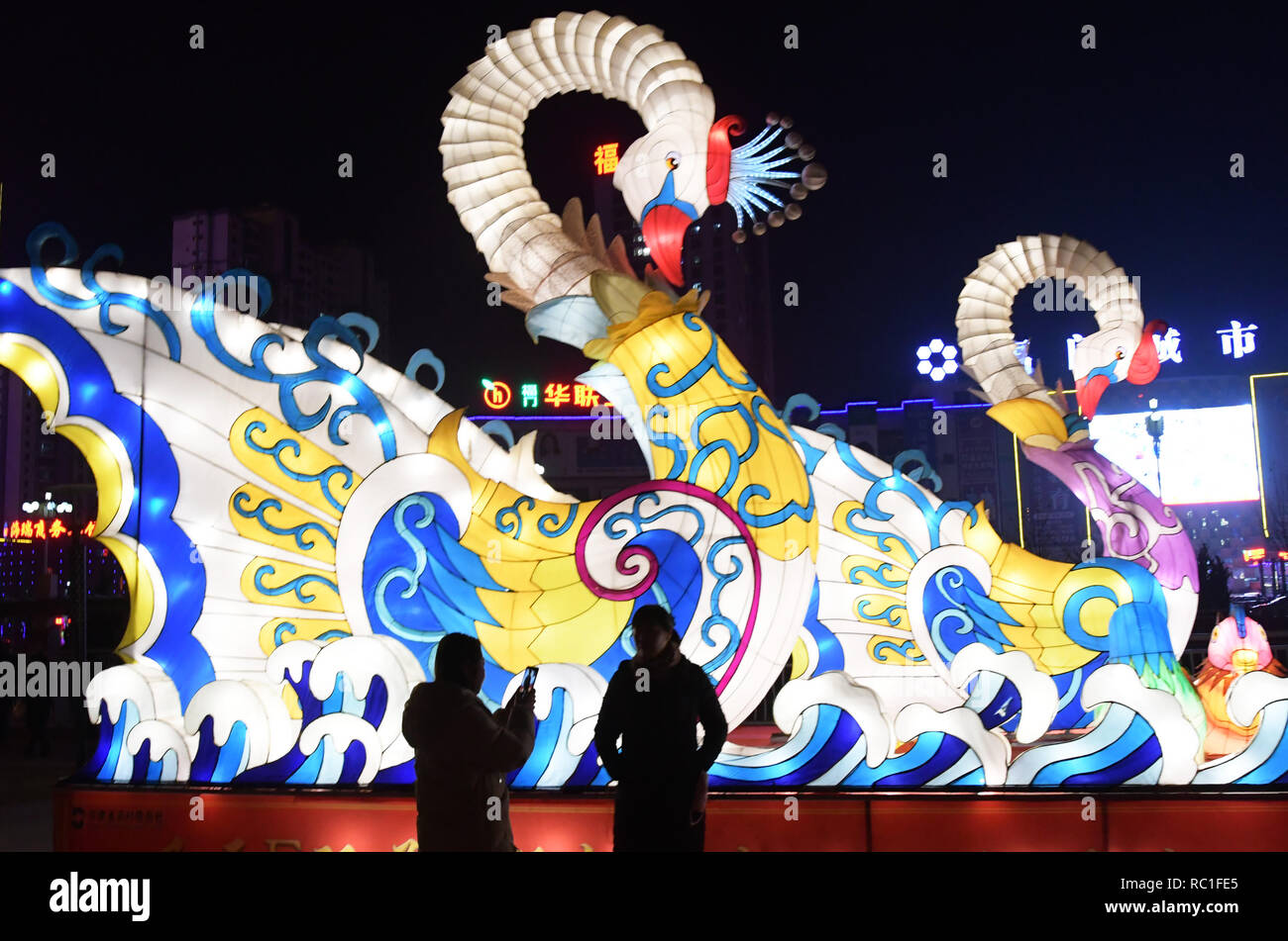 Linxia, China's Gansu Province. 12th Jan, 2019. Tourists view colored lanterns during a lantern festival for the upcoming Spring Festival, which starts from the first day of the first month of the Chinese lunar calendar, or Feb. 5 this year, at a waterfront park in Liujiaxia Township in Yongjing County, northwest China's Gansu Province, Jan. 12, 2019. Credit: Shi Youdong/Xinhua/Alamy Live News - Stock Image