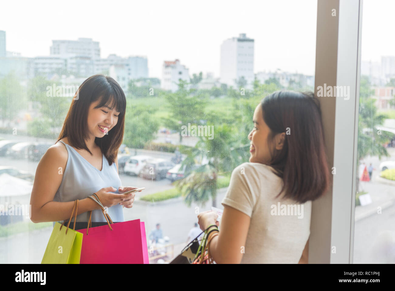 Two happy young ladies having nice time on shopping - Stock Image