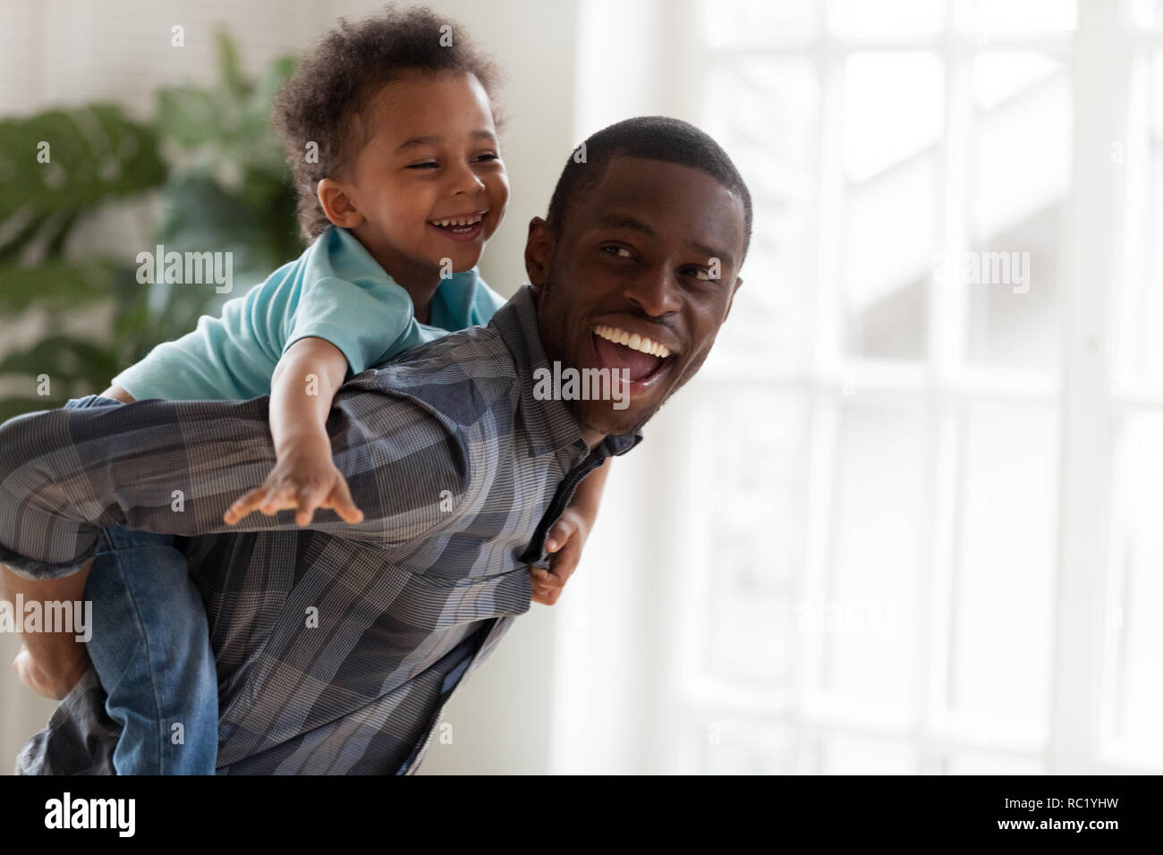 Excited kid boy playing with happy african father at home - Stock Image