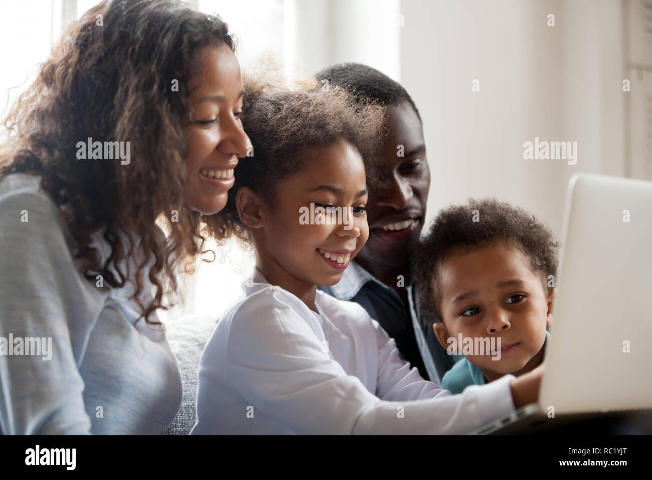 African parents and children laughing doing online shopping on l Stock Photo
