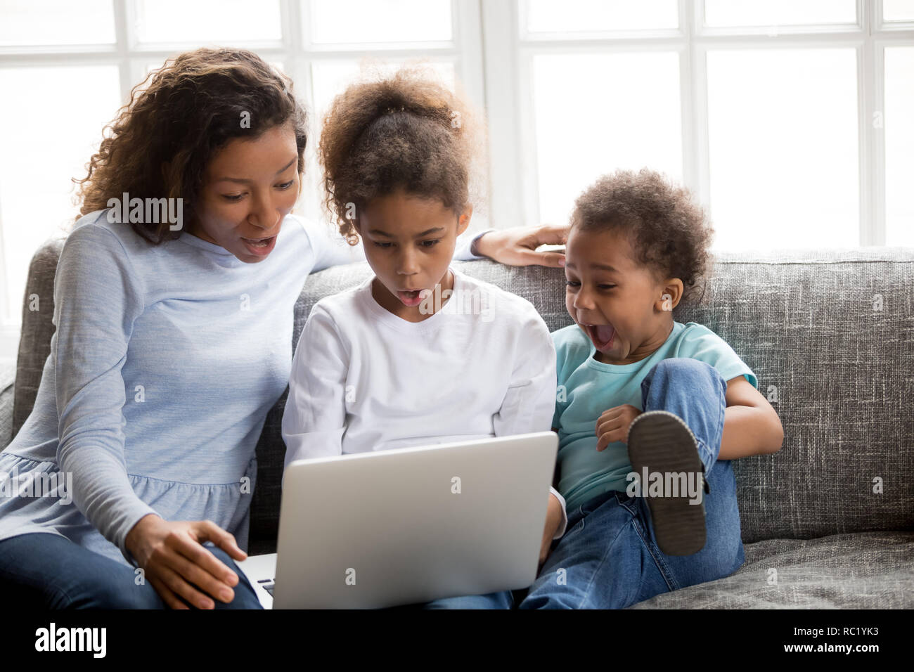 Excited african mom and kids looking at laptop feeling surprised - Stock Image