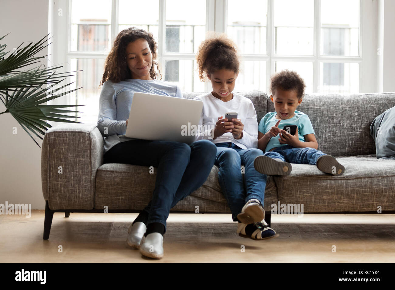 Black mom and kids using laptop phones addicted to devices - Stock Image