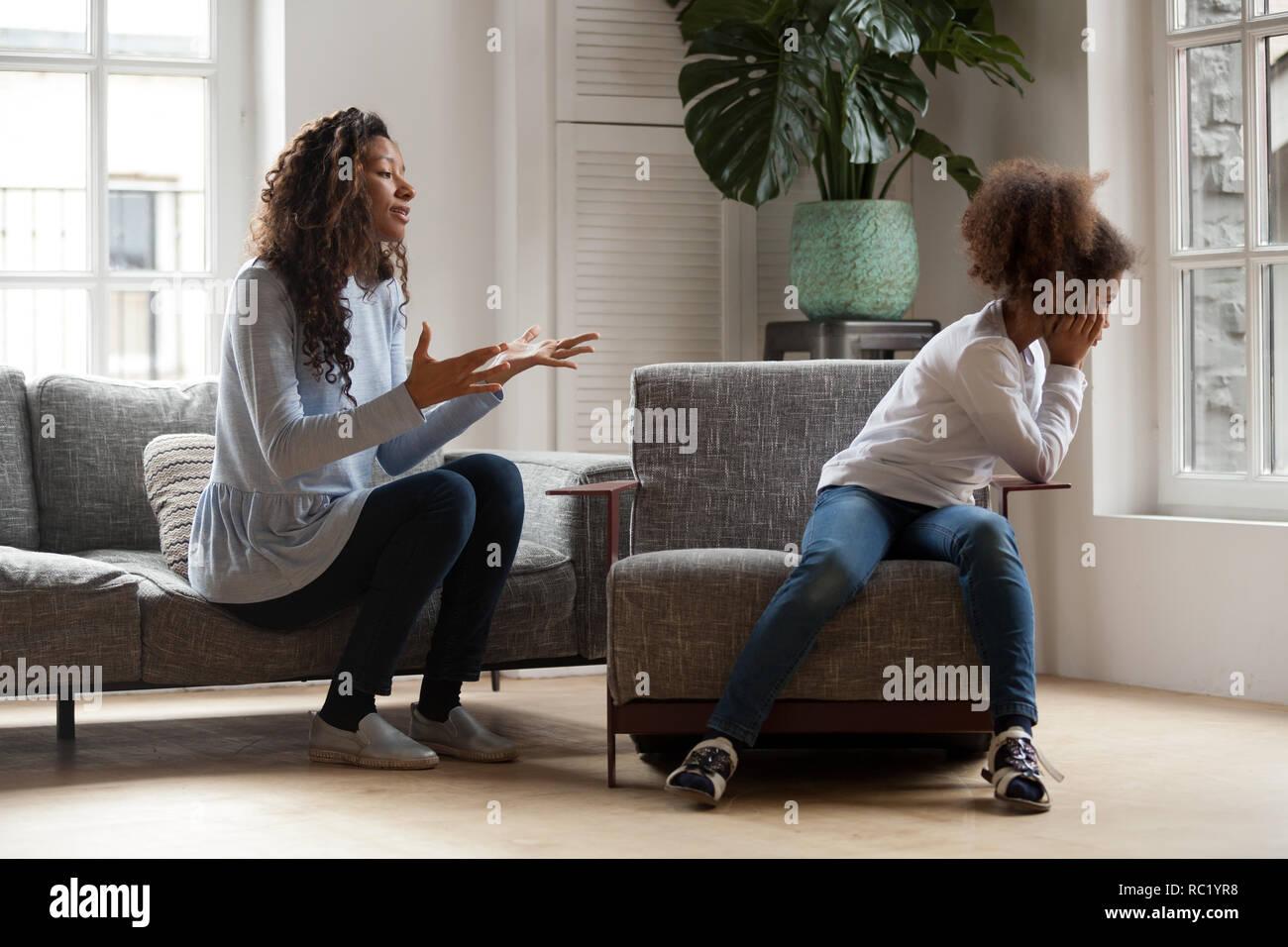 Stubborn african kid ignoring mom scolding, parent and child con - Stock Image