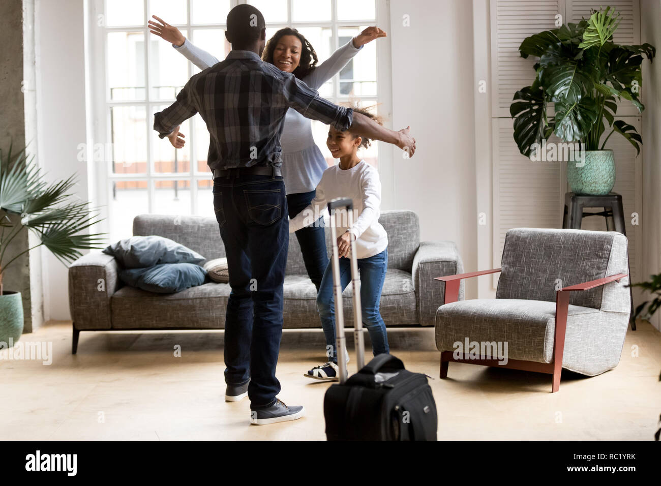 Happy black family excited to meet dad coming home - Stock Image