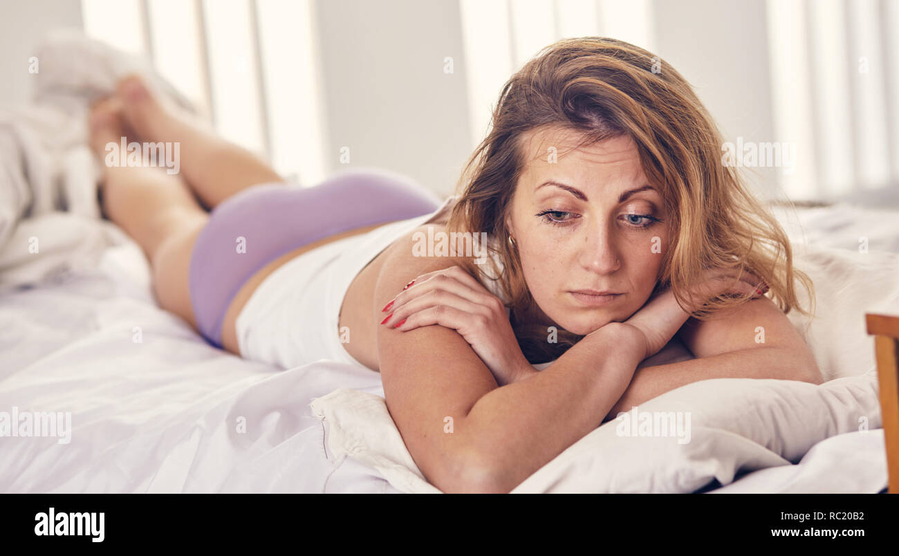woman worries about something in the morning in the bed - Stock Image