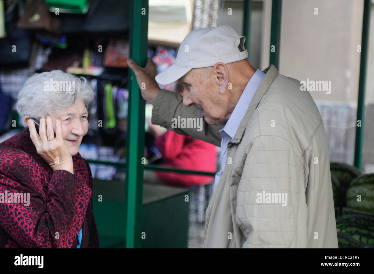 Elderly couple, with the woman talking on the cellphone, Latvia - Stock Image