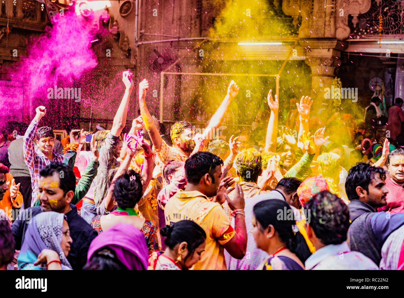 Barsana, India / February 23, 2018 - The crowd erupts in laughter and dance as powdered paint is thrown in the air during Holi festival - Stock Image