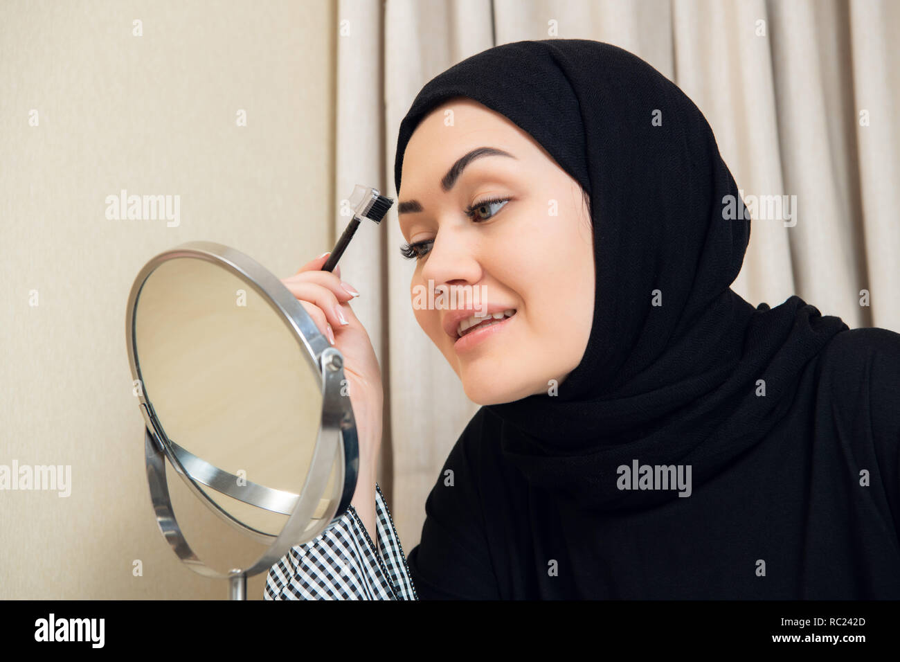 A young muslim woman shaping her eyebrows with a brush - Stock Image