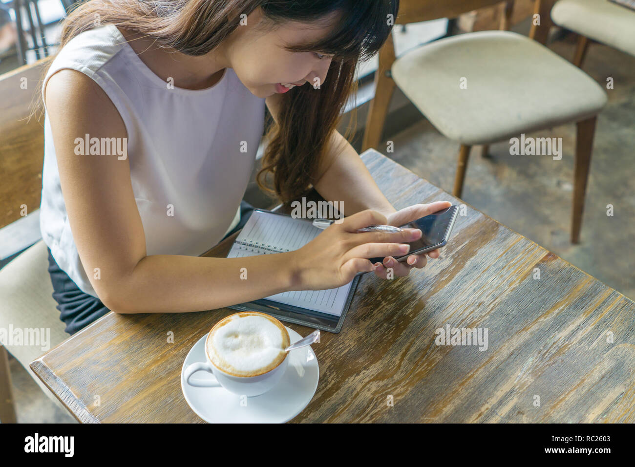 Smiling girl tapping smartphone screen - Stock Image
