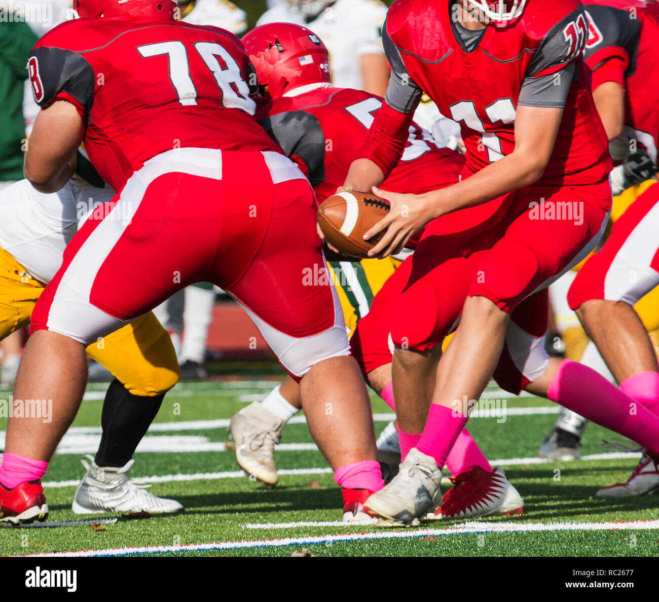 Quarterback turning to look for someone to hand off the ball to just after the snap during a high school football game - Stock Image