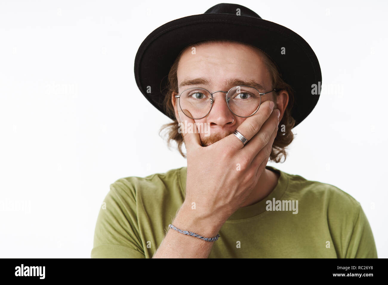 Gosh what have I done. Portrait of stunned shocked guy feeling regret holding hand on mouth looking uneasy and anxious as making mistake standing unaware how solve troublesome situation - Stock Image