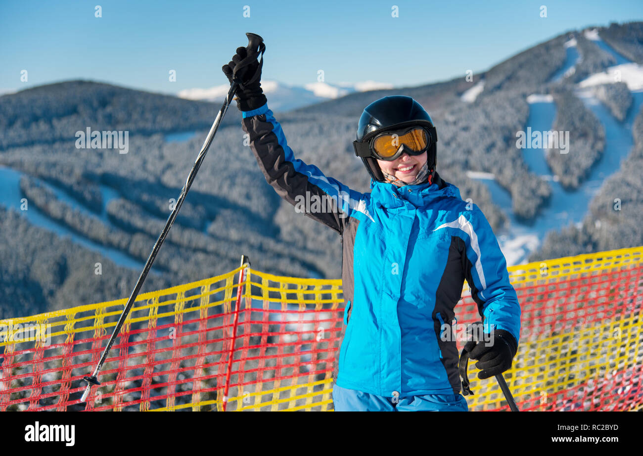 Woman enjoying ski holiday standing on the snowy mountain and raised her hand up at sunny day. Woman at ski resort wearing helmet, blue ski suit and g - Stock Image