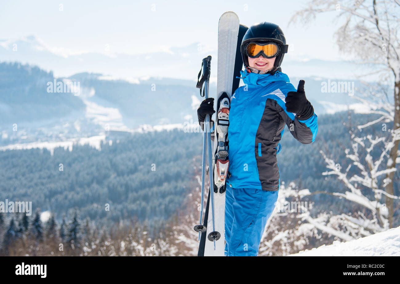 Happy woman skier wearing blue ski suit, black helmet and mask smiling, showing thumbs up in the mountains - Stock Image