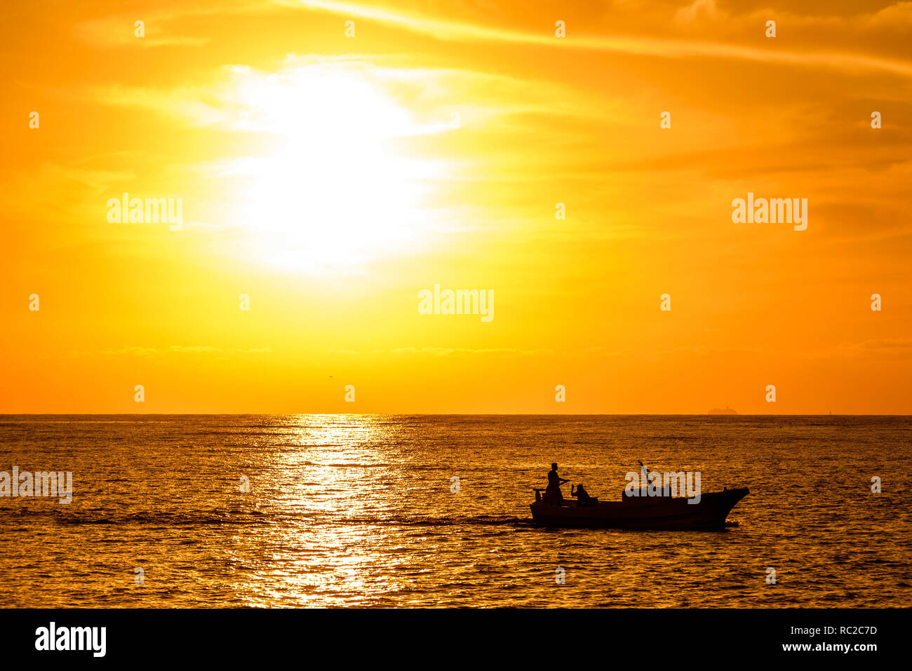 Setting Sun Spotlights Solitary >> Silhouette Of A Fishing Boat Passing In Front Of An Orange Sunset