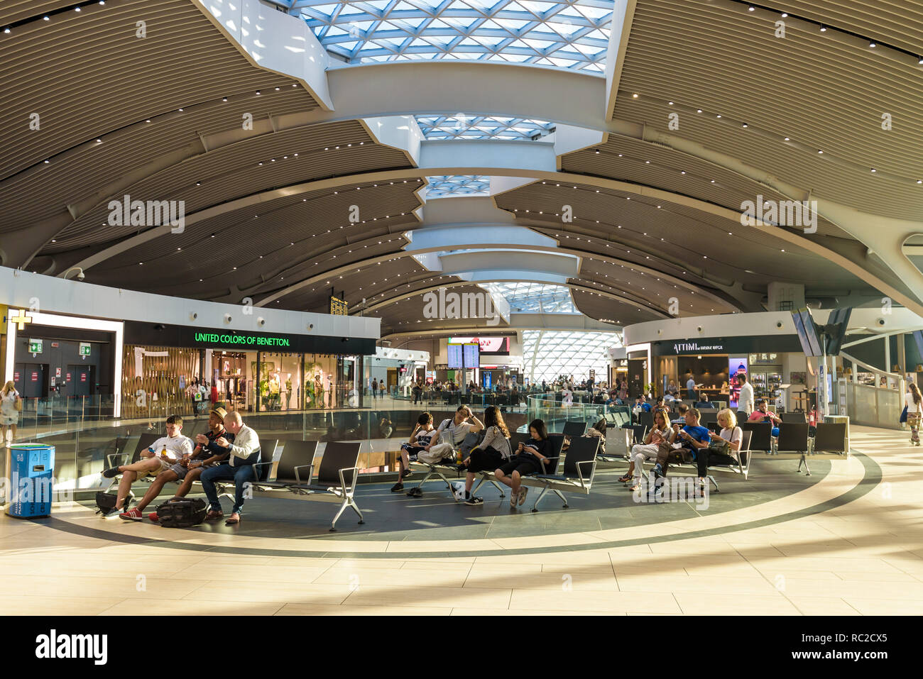 Rome Fiumicino international airport. People waiting for flights and connections inside the terminal with duty free shops and restaurants. - Stock Image