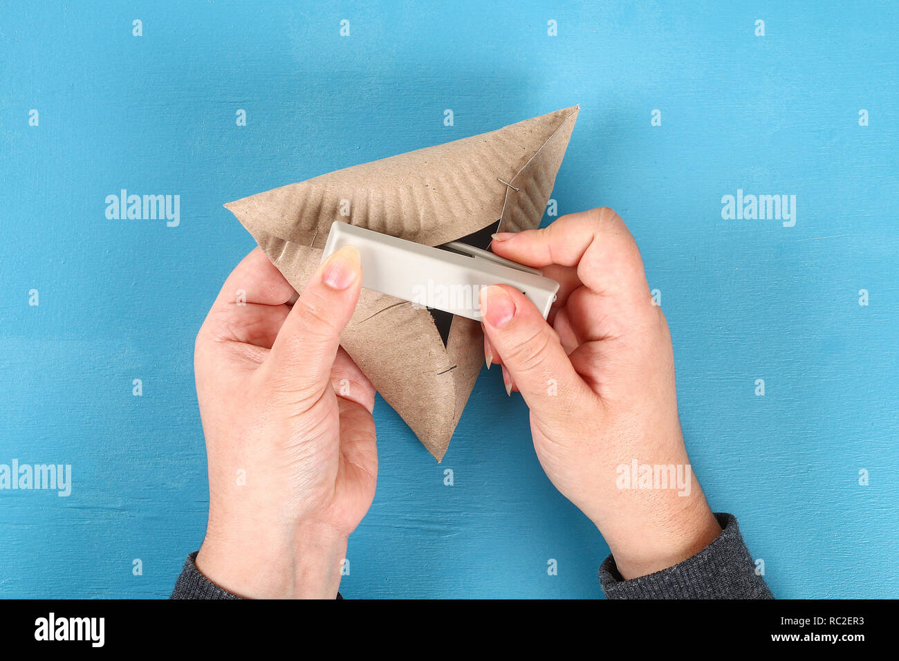 Purim. Diy cookies hamantaschen of cardboard plates with sweet surprise inside on blue background. Gift ideas for children, decor to Purim. Handmade.  - Stock Image