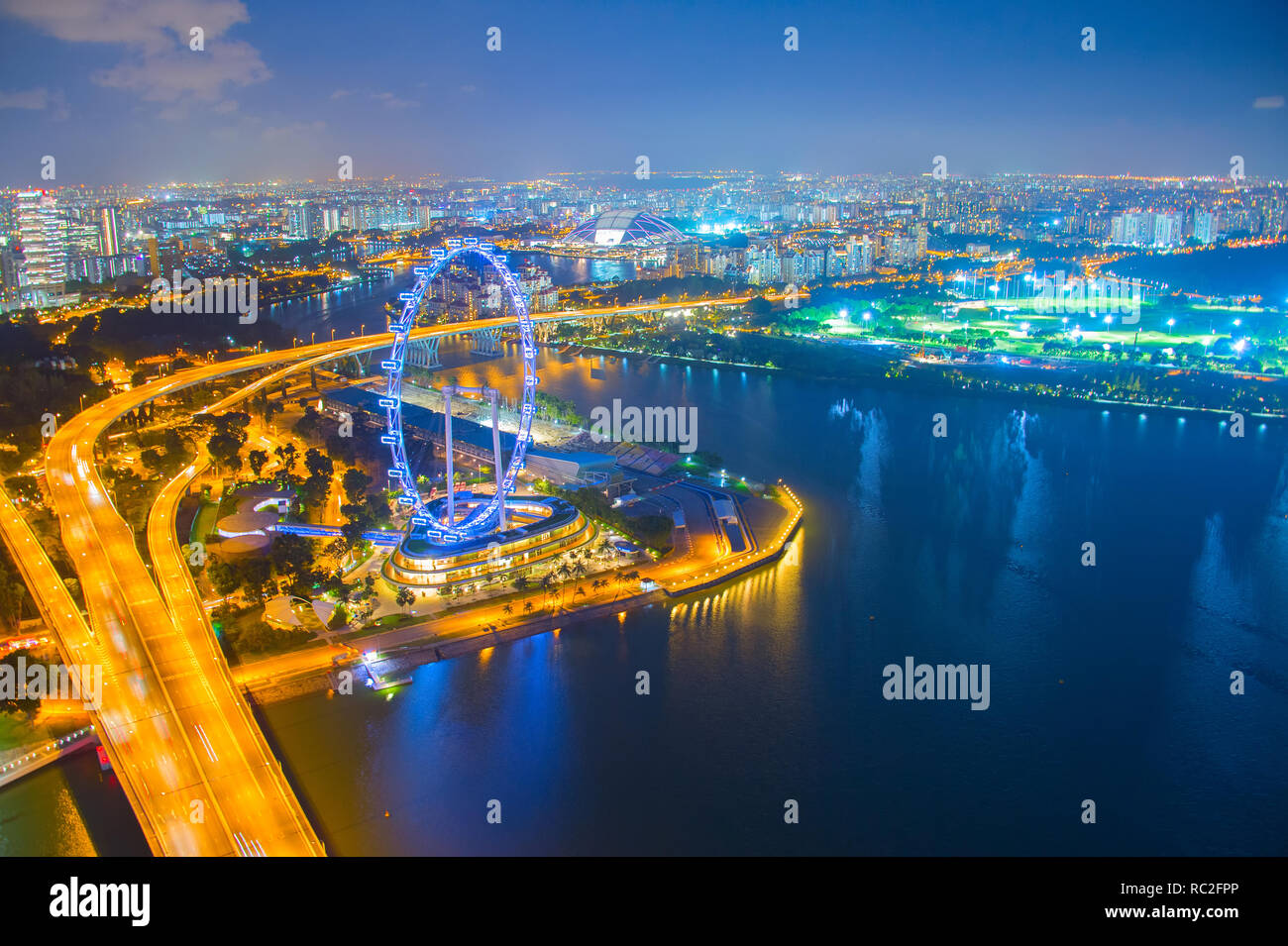 Aerial view of illuminated Singapore metropolis at night, embankment with ferris wheel ad city highway - Stock Image