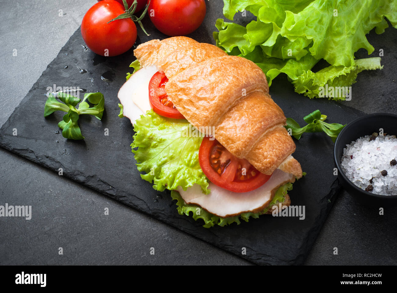 Croissant sandwich with ham, cheese, lettuce and tomato - Stock Image