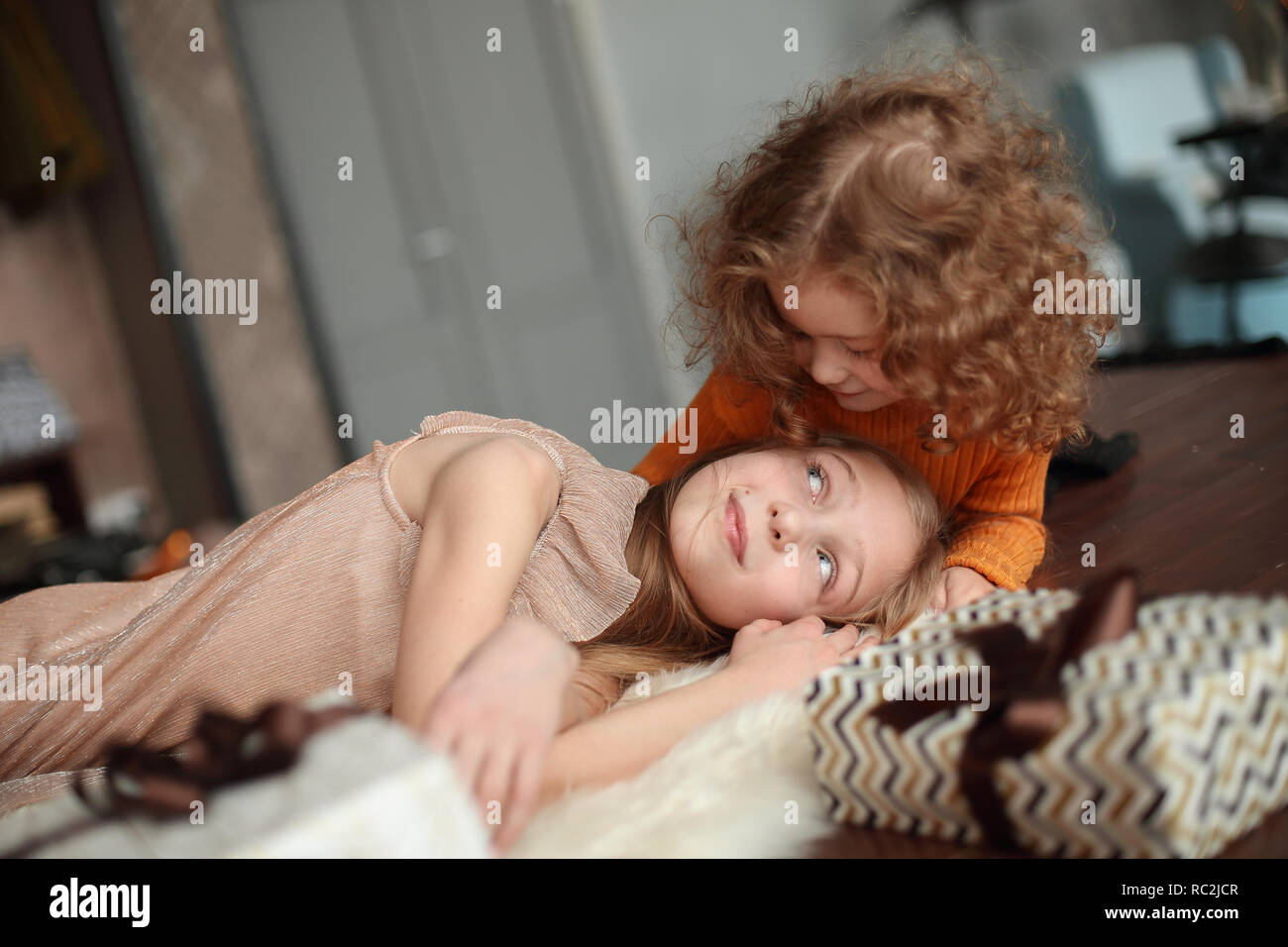 two pretty sisters relaxing in the living room on Christmas eve. Stock Photo