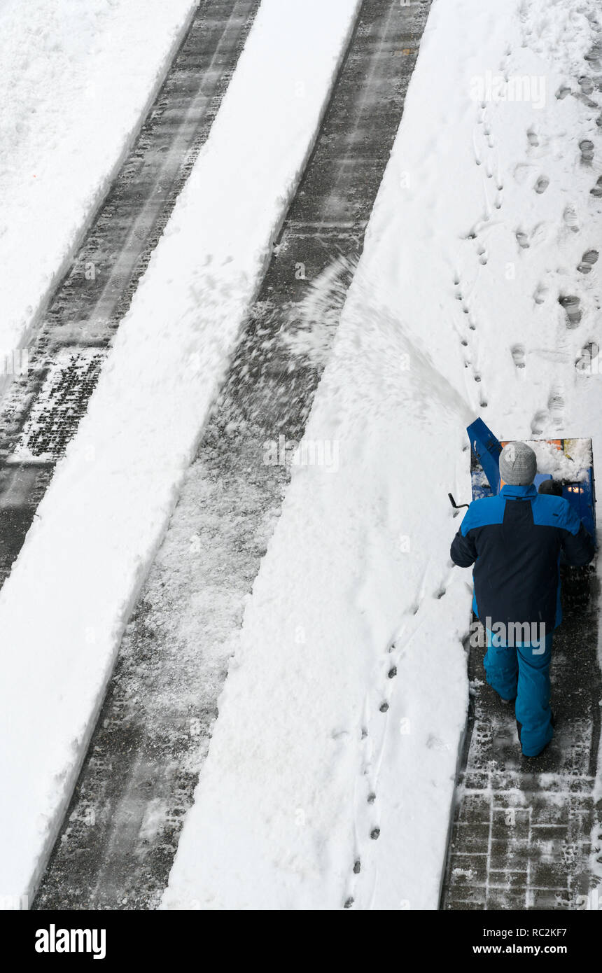 man with a snow blower clears snow from a road after a heavy snowfall in the Swiss Alps in winter - Stock Image