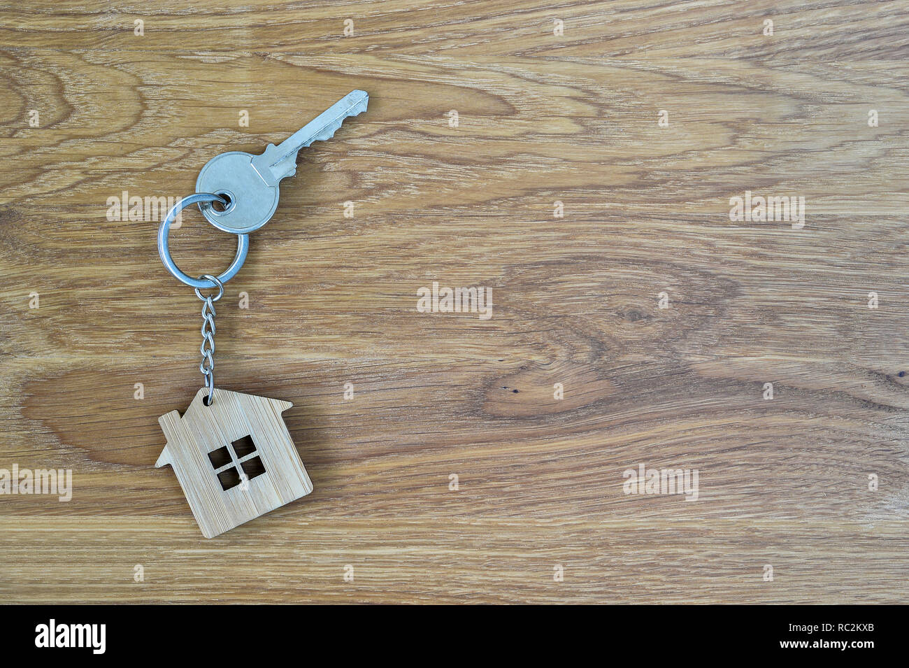 Metal house lock key in the form of bamboo keychain on wooden oak background. Real estate purchase offer concept. Copy space. - Stock Image