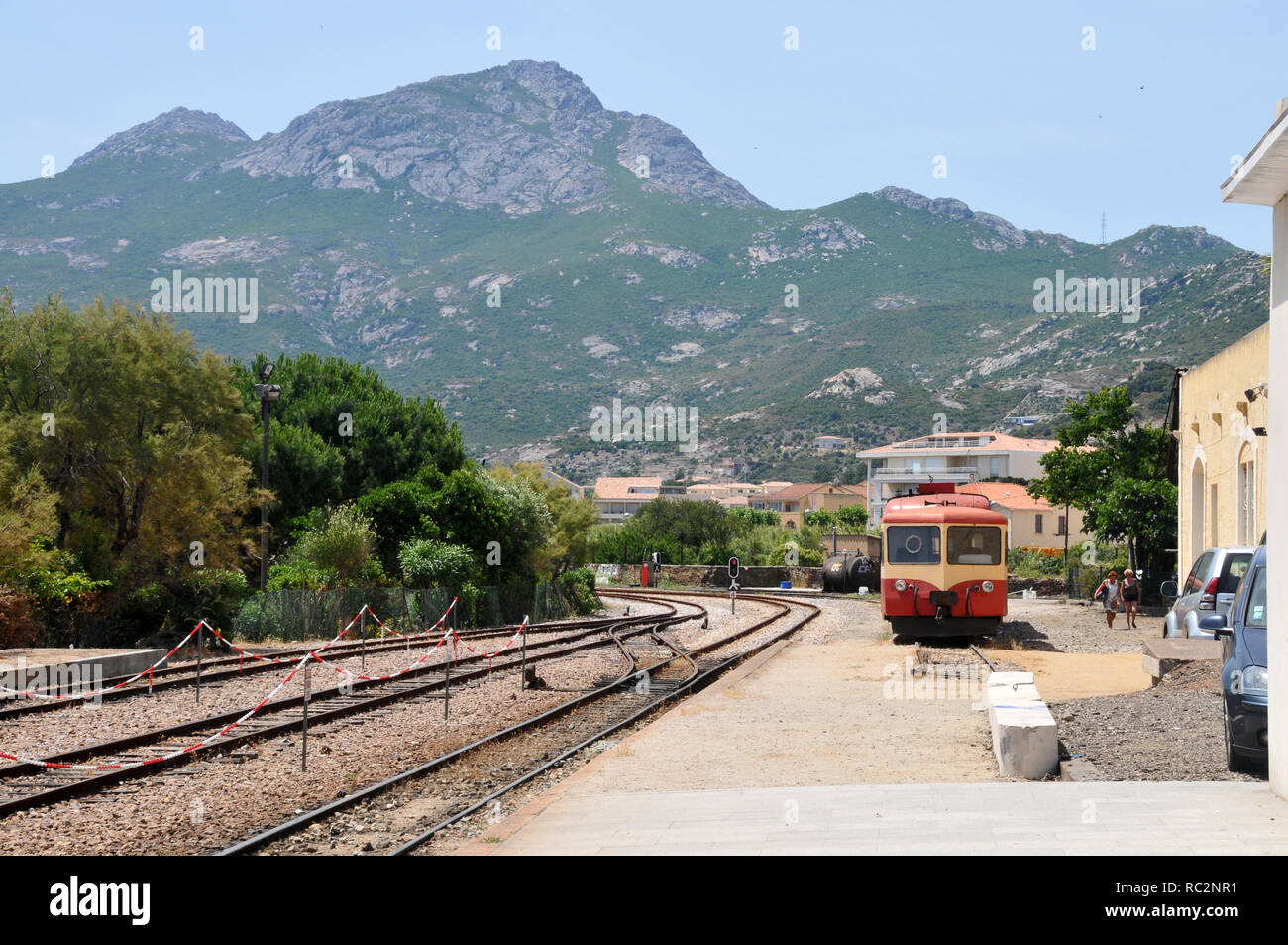 A couple of passengers making their way to the train Station in Calvi - Stock Image
