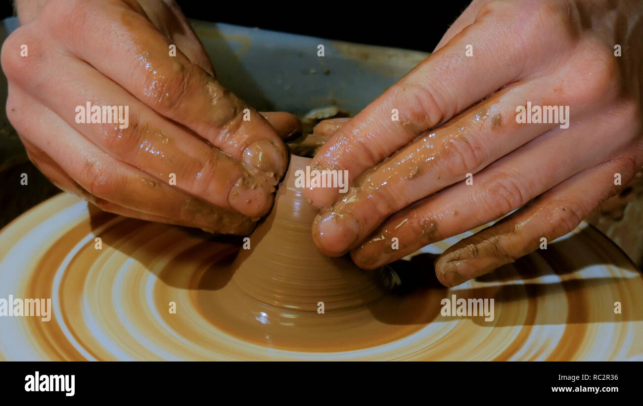 Professional male potter working in workshop, studio. Close up shot of potter's hands. Handmade, small business, crafting work concept - Stock Image