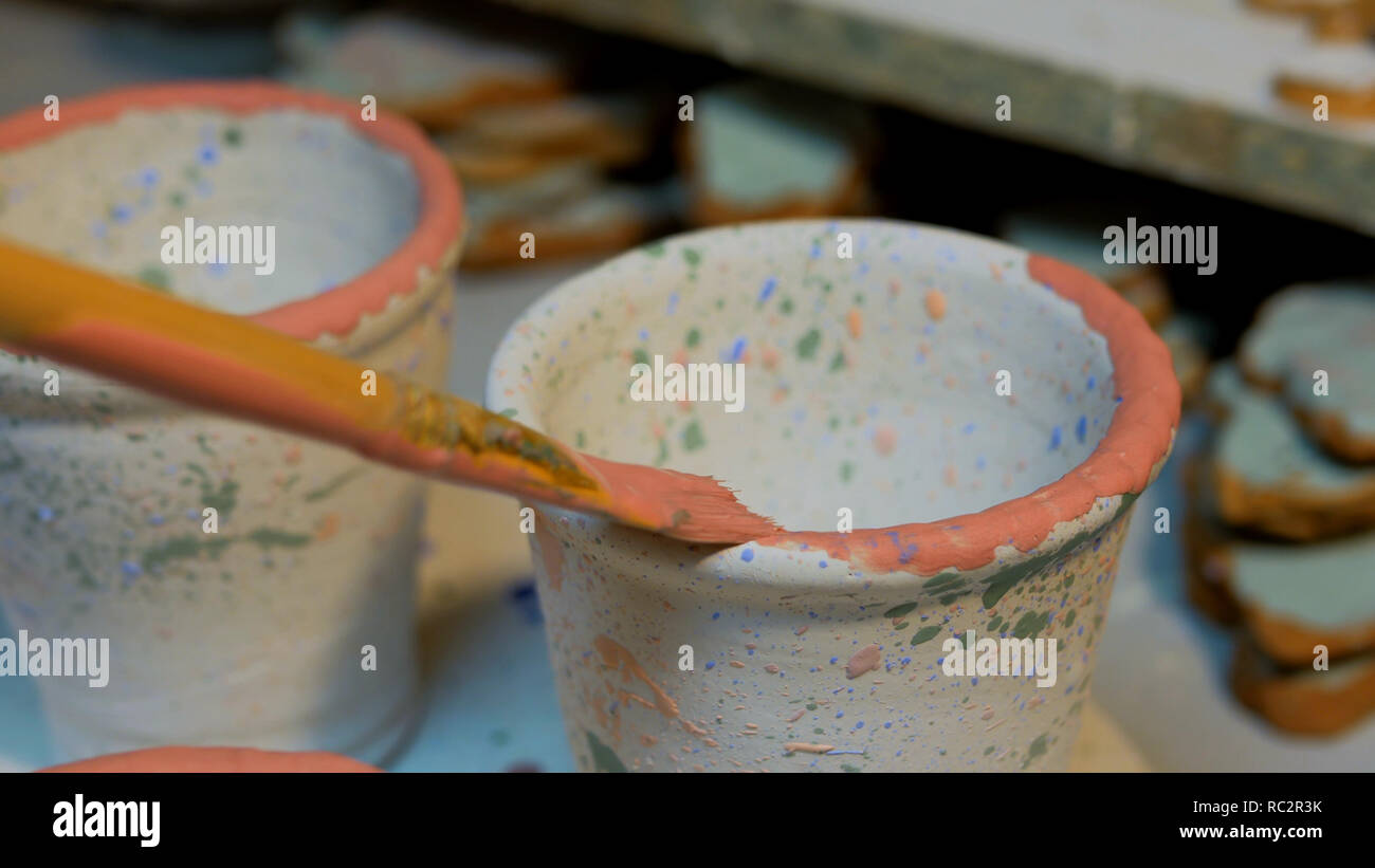 Professional male potter painting mugs in pottery workshop, studio. Crafting, artwork and handmade concept - Stock Image
