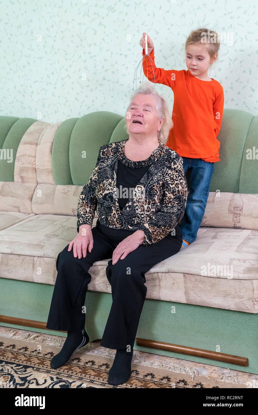 granddaughter massages grandmother head - Stock Image