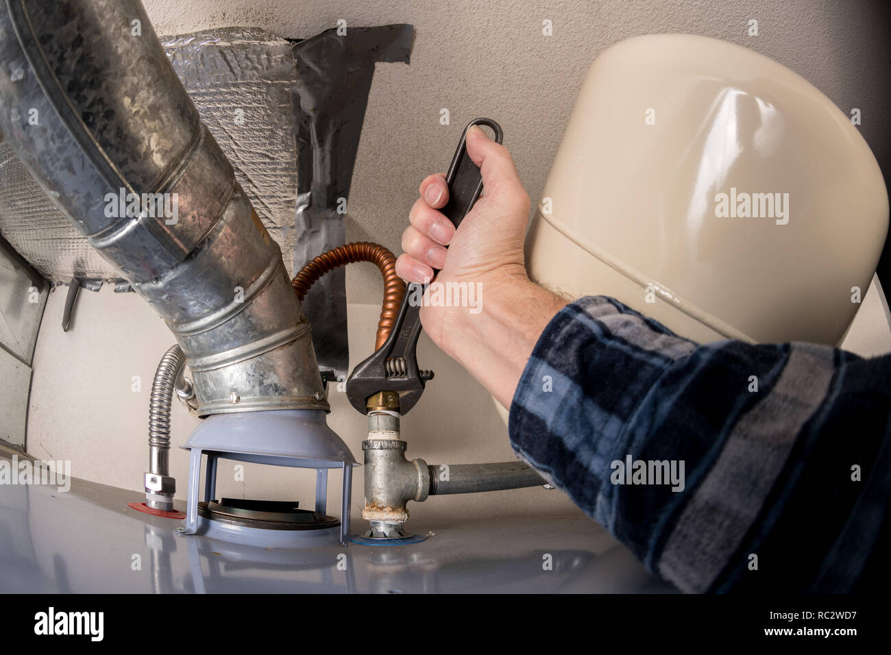 Adjustable wrench tightening a pipe on a water heater by a plumber - Stock Image