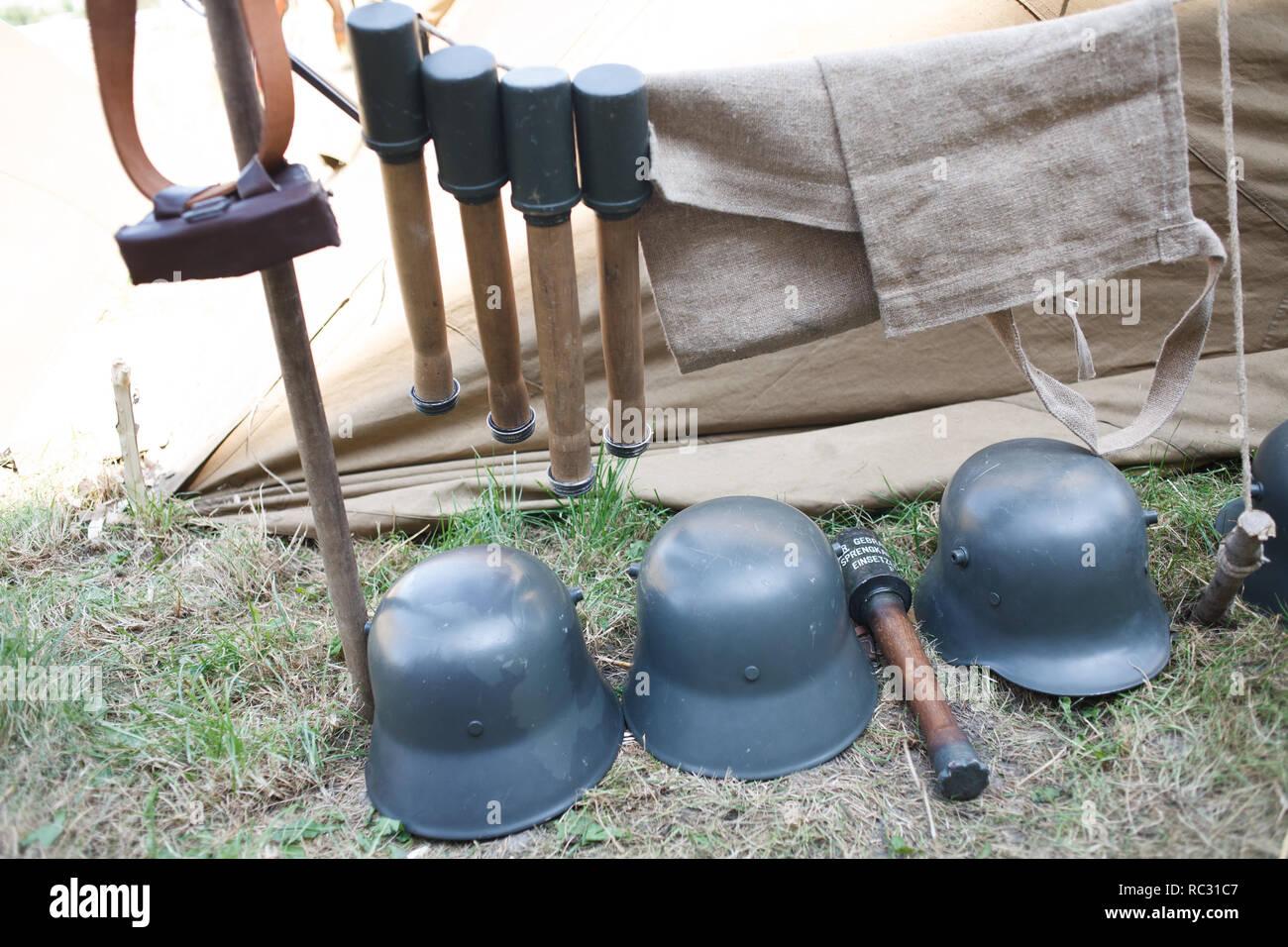 Rifles pyramids with ammunition and german steel helmet, First World War-era reenactment - Stock Image