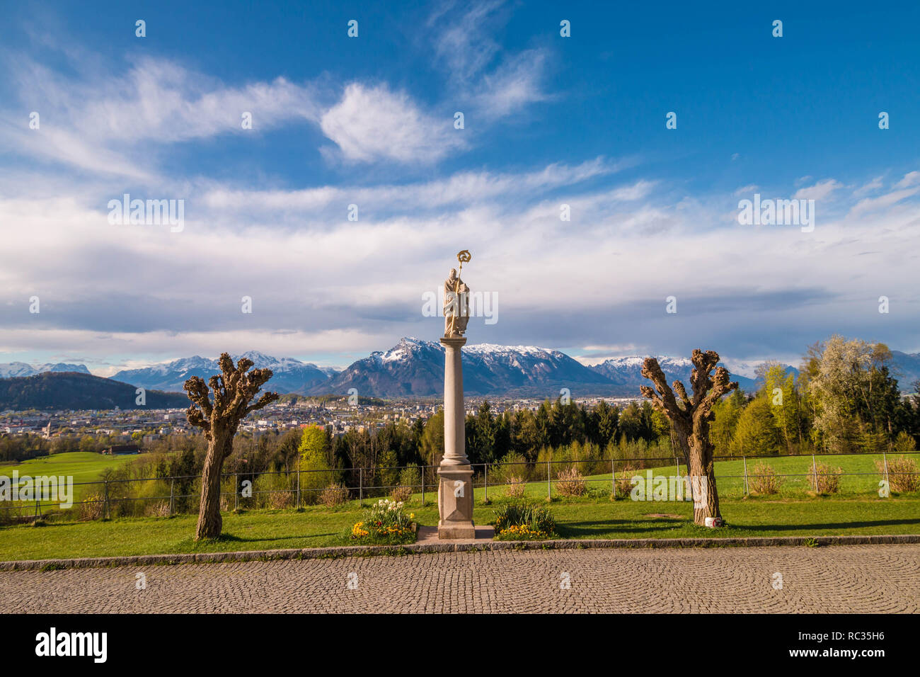 Statue of St.Rupert and a beautiful panoramic view of Salzburg and Alps from Maria Plain in Berghein bei Salzburg, Austria - Stock Image