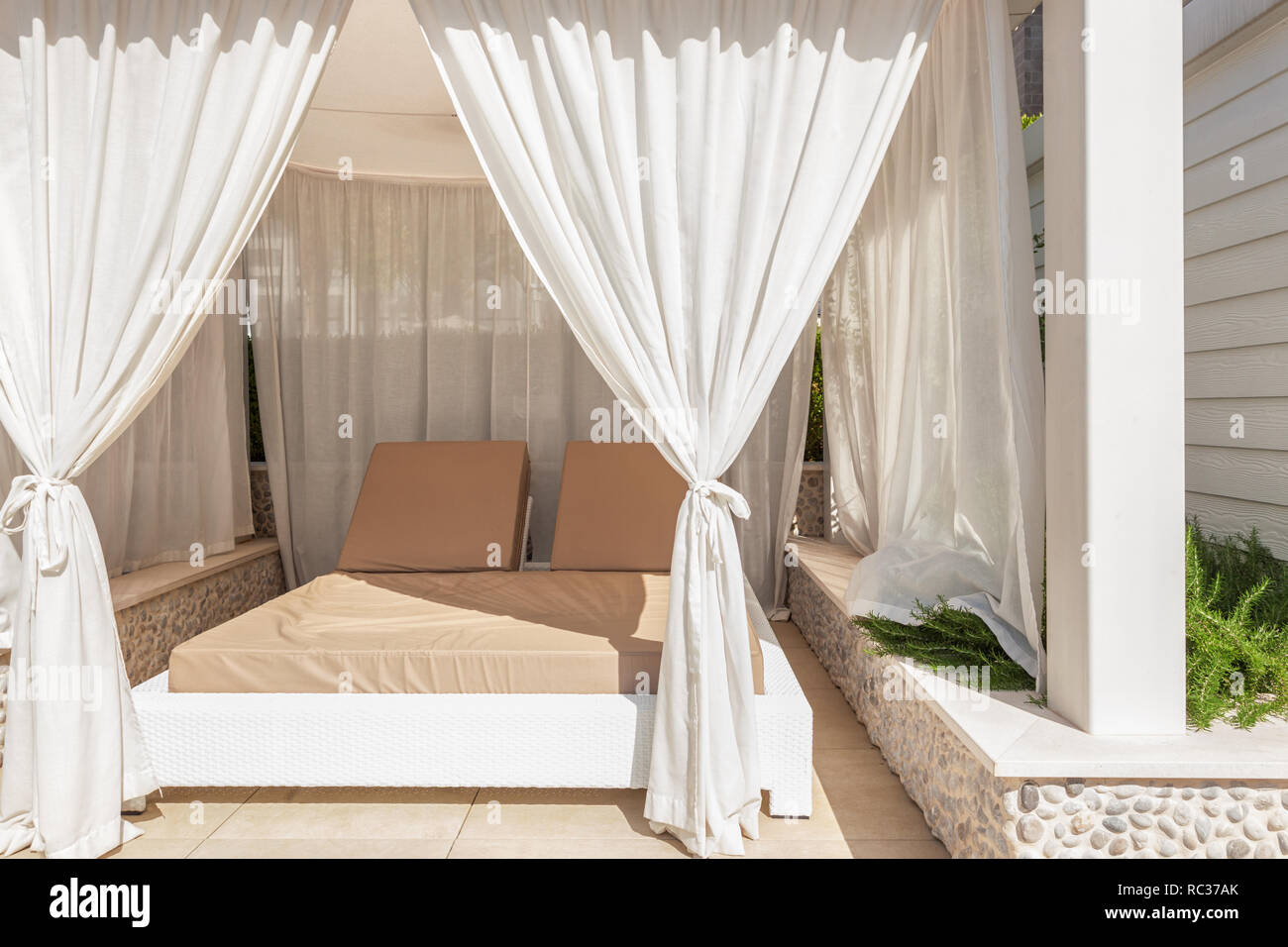 Sunbed lounge with curtain for luxury summer relaxation concept - Stock Image