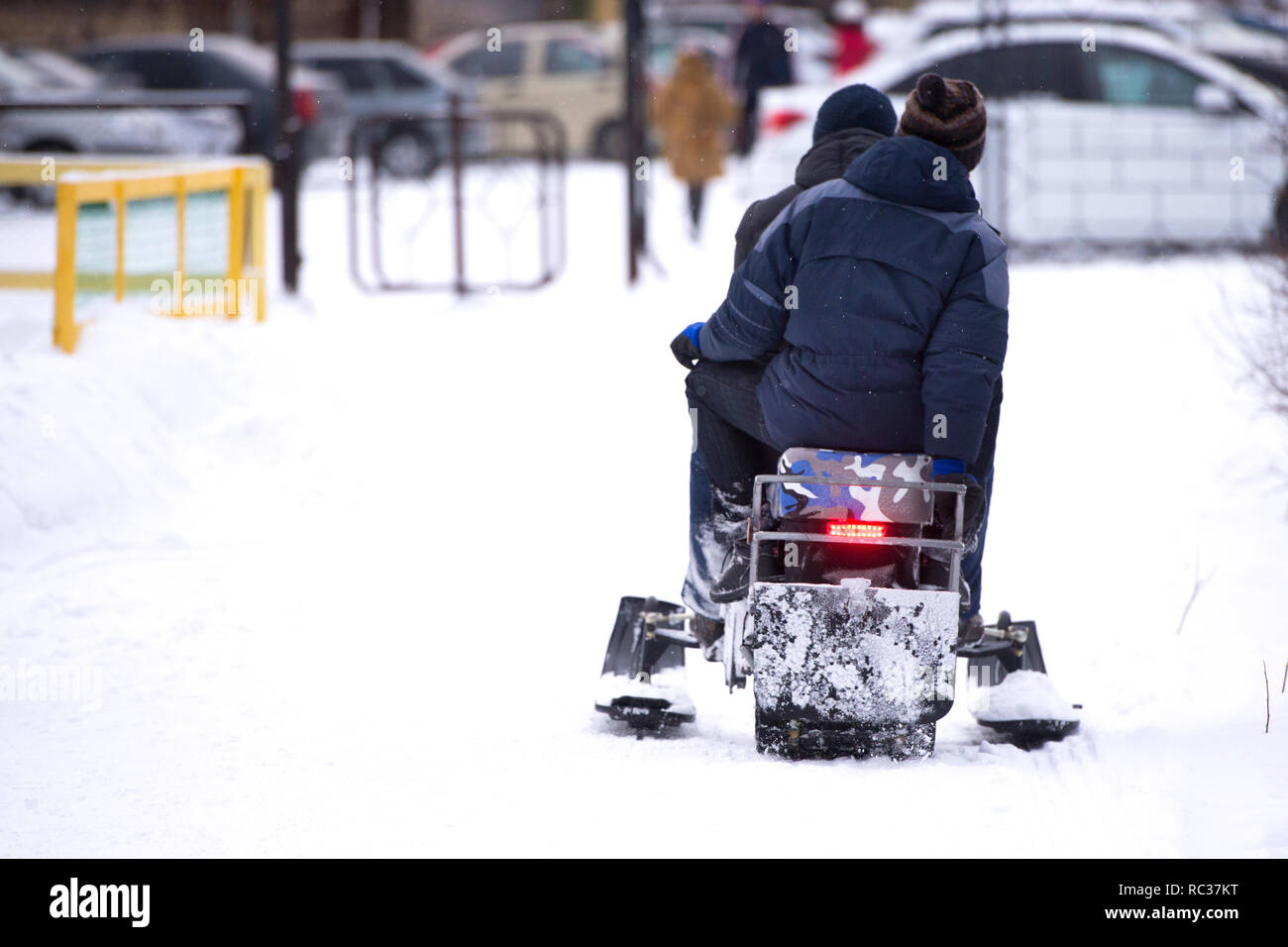 People riding a snowmobile action - Stock Image