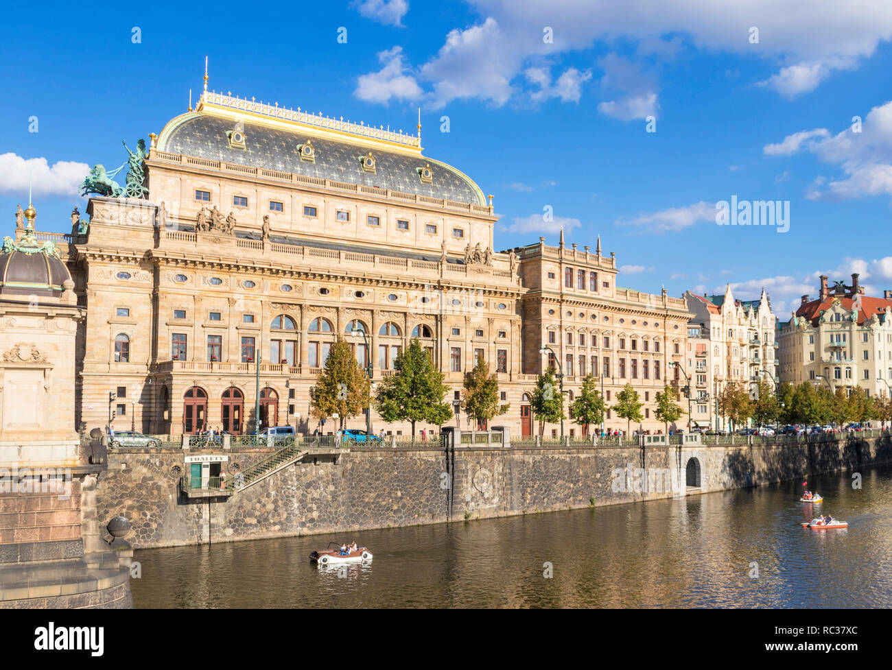 Prague National Theatre Národní divadlo on the banks of the river Vltava with people on the river in boats Prague Czech Republic EU Europe - Stock Image