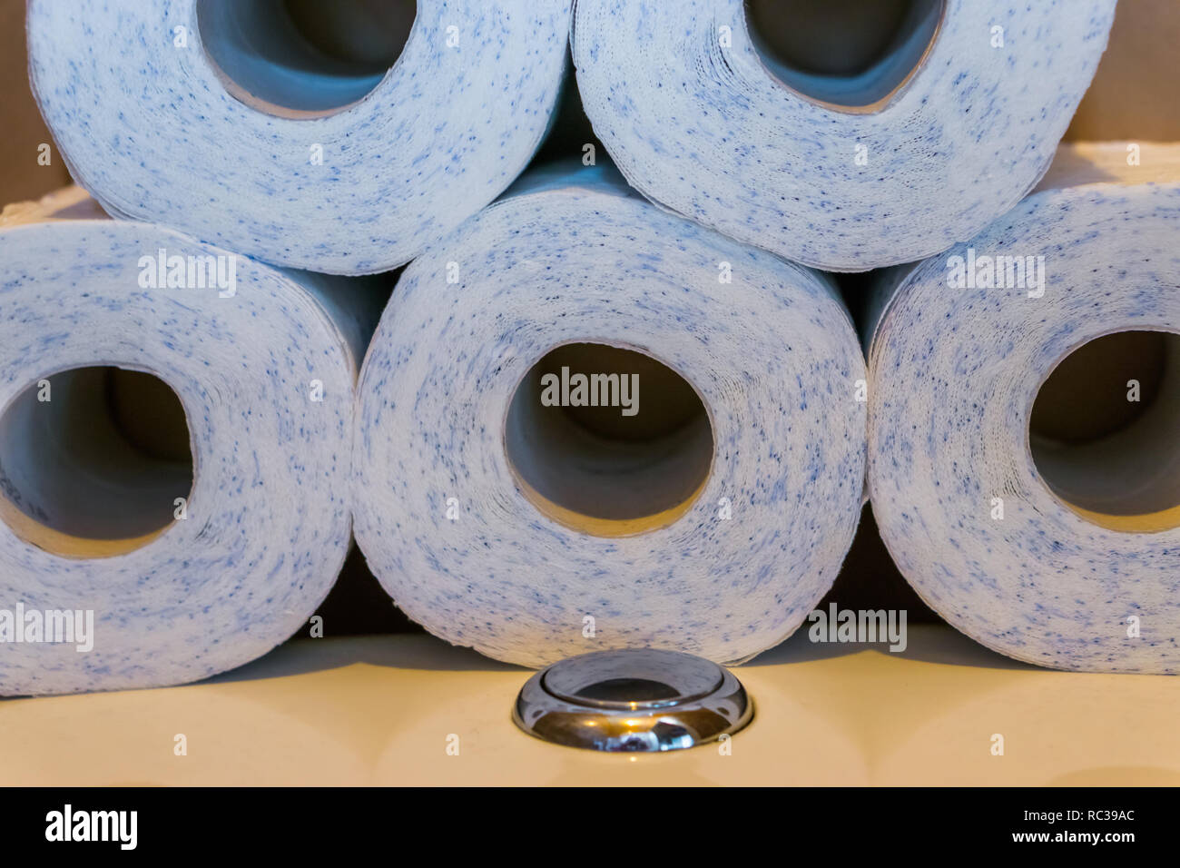 piled stack of toilet paper laying on the water closet, household products, bathroom background - Stock Image
