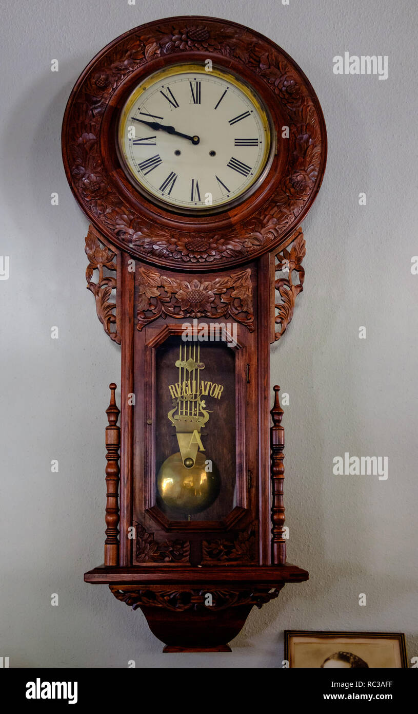 Antique Regulator ornate carved wooden pendulum wall clock with Roman Numerals clock face. - Stock Image