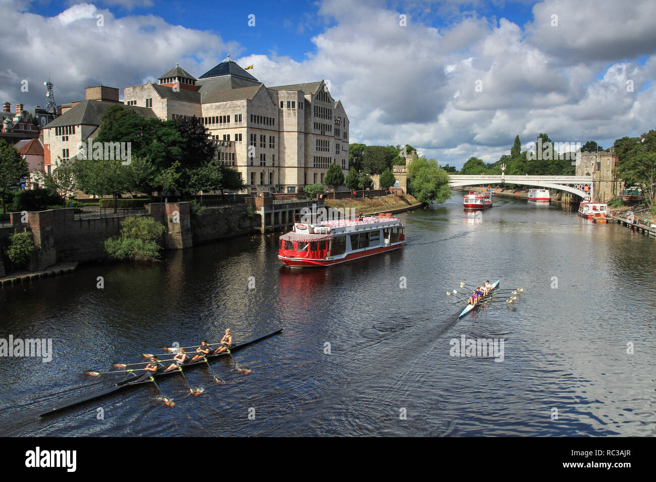 YORK, UK - SEPTEMBER 2, 2015.  A river cruise boat and rowing club boats sailing along the River Ouse in the centre of the historic City of York, UK - Stock Image