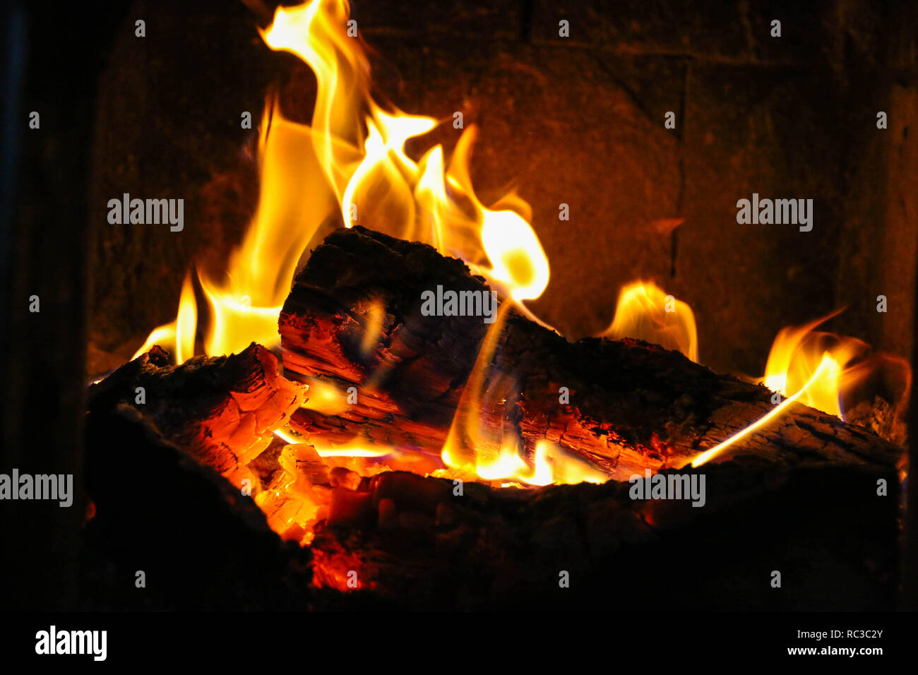Fire burning in a tiled stove. - Stock Image